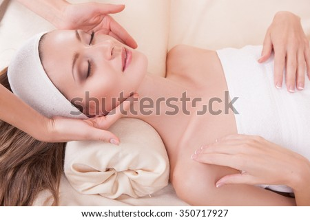 Attractive girl with perfect skin.Haired woman close up while lying on the massage table, her face massaged his hands beautician, a smile on his face.Woman and facial massage.Woman and spa. - stock photo
