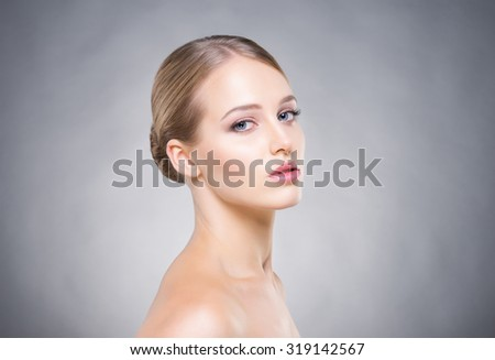 Attractive girl with smooth skin over the grey background. - stock photo