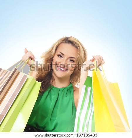 Attractive girl with some shopping bags over blue background - stock photo