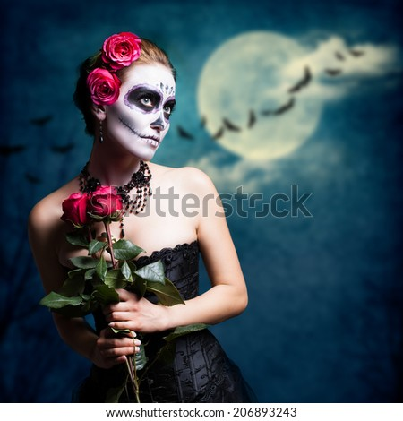 attractive girl with sugar skull styling with a full moon background - stock photo