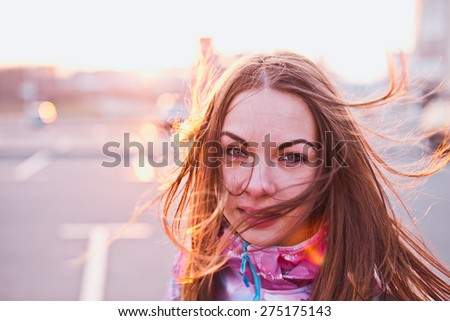 Attractive girl with wind fluttered hair looking in a camera on a parking lot at a sunset. Traveling, life and freedom concept. Copy space - stock photo