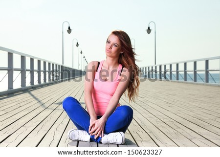 Attractive girl Young woman on pier Sits Crossed Legged Relaxing Old Wooden Pier - stock photo