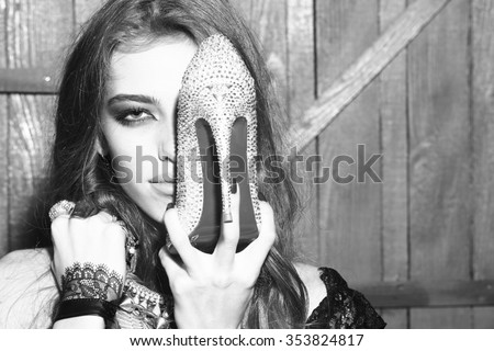 Attractive glamour young fashionable girl with long curly hair bright makeup and costume jewellery of necklace rings and earrings holding diamond shoe with high heel on wooden background, horizontal - stock photo