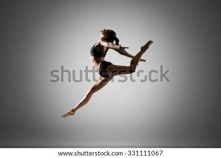 Attractive gorgeous young fit woman in sportswear doing sport practice, dancing, art gymnastics, gymnast jumping high, full length, studio image on gray background - stock photo