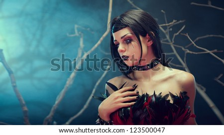 Attractive gothic girl in spiked choker, studio shot with fog and branches - stock photo
