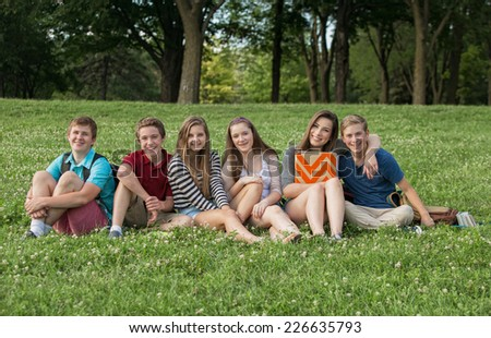 Attractive group of Caucasian teen students outdoors - stock photo