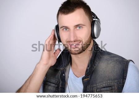 Attractive guy holding headphones listening to music - stock photo