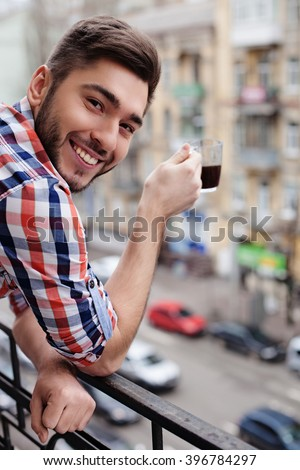 Attractive guy is drinking a cup of beverage - stock photo