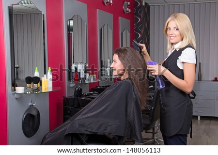 attractive hairdresser makes hairstyle for young attractive girl - stock photo