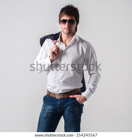 Attractive handsome man in casual clothes wearing glasses and holding jacket in his hand - stock photo