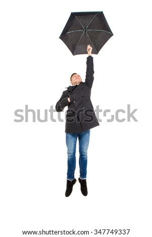 Attractive handsome young man in black coat and jeans flying with umbrella over white background - stock photo