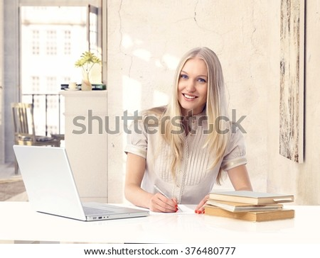 Attractive happy blonde casual caucasian woman studying at vintage home. Smiling, sitting at table with laptop computer, books and paper, writing, looking at camera. - stock photo
