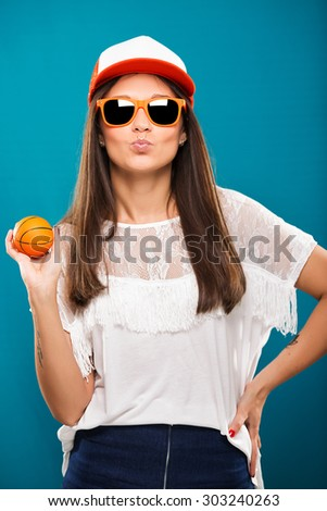 Attractive happy brunette girl with little ball in her hand, wearing in white blouse, red and white cap and orange sunglasses, is posing on blue background, waist up - stock photo