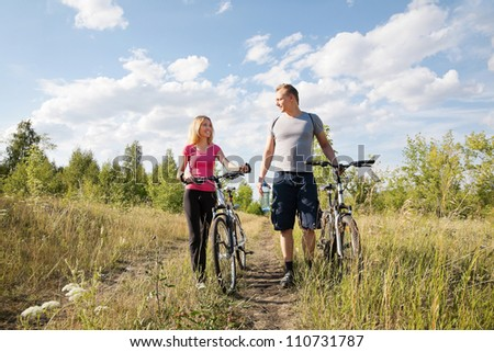 Attractive happy  couple having conversation during biking - stock photo