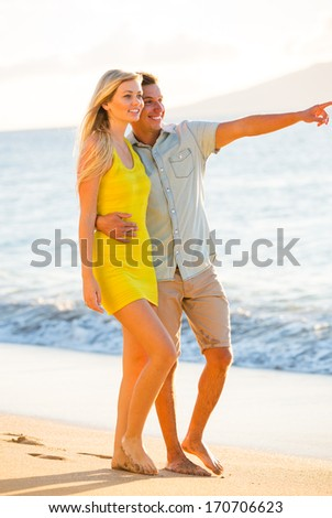 Attractive Happy Couple Walking on the beach at Sunset, Romantic Vacation - stock photo