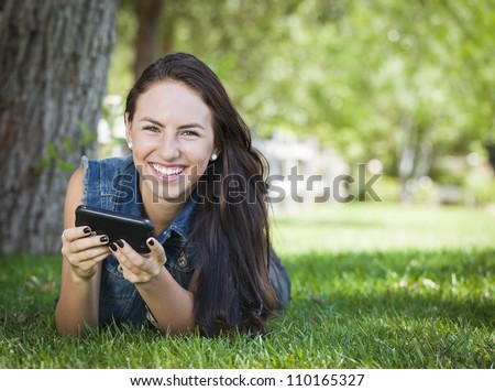 Attractive Happy Mixed Race Young Female Texting on Her Cell Phone Outside Laying in the Grass. - stock photo