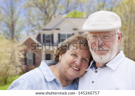 Attractive Happy Senior Couple in Front Yard of House. - stock photo