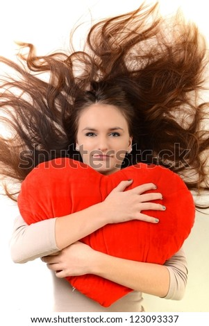 Attractive happy smiling brunette young girl holding one little red valentine heart, woman sitting on couch at home, concept of valentine's day - stock photo