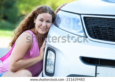 Attractive happy woman sitting near own new vehicle - stock photo