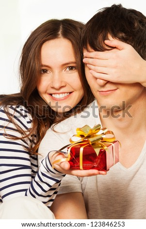 Attractive happy woman with big toothy smile holding husband eyes giving him a present for Valentine's day - stock photo