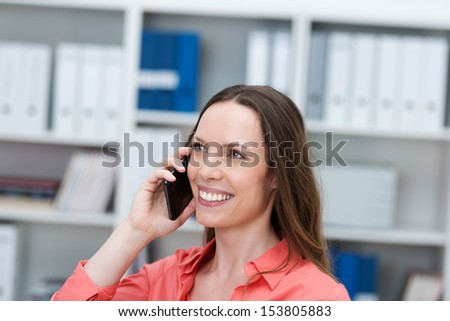 Attractive happy young businesswoman chatting on a smartphone in the office with a delighted smile on her face - stock photo