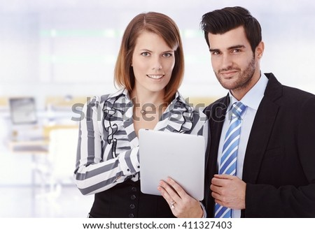 Attractive happy young caucasian businesswoman with tablet computer and handsome colleague at business office. Smiling, looking at camera, suit, copyspace. - stock photo