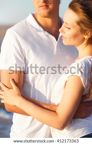 Attractive happy young couple cuddling at the beach. Close up - stock photo