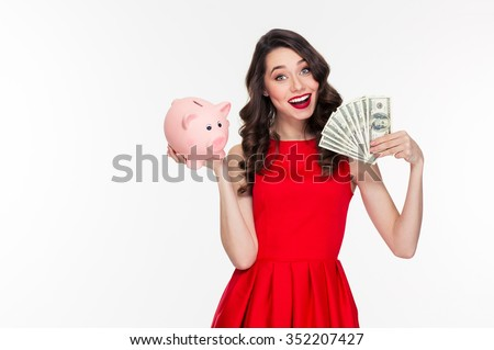Attractive happy young curly woman with bright makeup in retro style holding piggy bank and money - stock photo