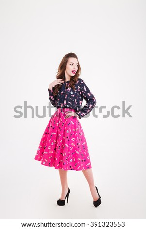 Attractive happy young woman in black high heels shoes standing and posing over white background - stock photo