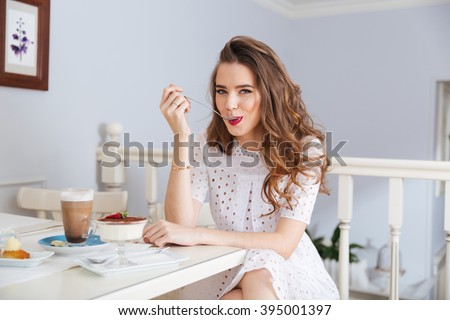 Attractive happy young woman sitting and eating dessert in cafe - stock photo