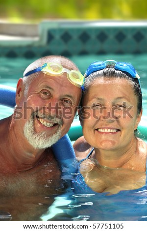 Attractive, healthy older couple swimming together - stock photo