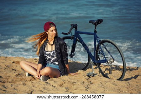 Attractive hipster girl relaxing on the beach after ride on her sport fixed gear bicycle, young woman sitting on the sand enjoying sunny afternoon at holiday, charming female with rental bike outdoors - stock photo