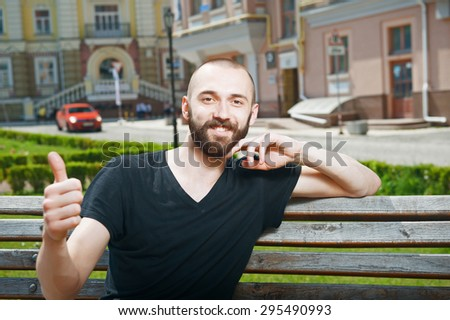 Attractive hipster guy is smiling and showing his thumb up. He is sitting on the bench in the city - stock photo