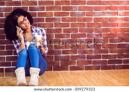 Attractive hipster sitting and phoning with smartphone against red brick background - stock photo