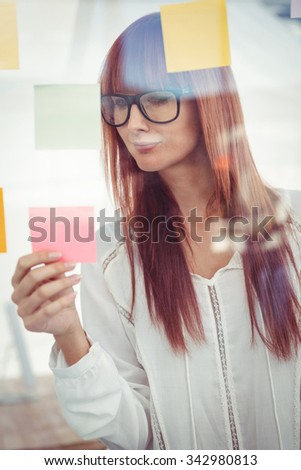 Attractive hipster woman looking at sticky notes in her office - stock photo