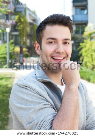 Attractive hispanic guy on outdoors laughing at camera - stock photo