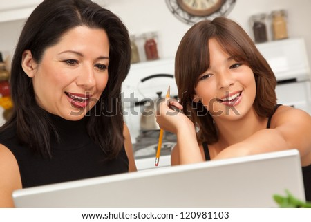 Attractive Hispanic Mother and Mixed Race Daughter in the Kitchen using the Laptop Computer Together. - stock photo