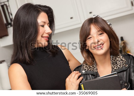 Attractive Hispanic Proud Mom with Her Pretty Schoolgirl Daughter in the Kitchen. - stock photo
