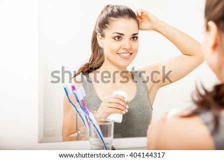 Attractive Hispanic young woman putting on deodorant while looking at herself in a mirror in the bathroom - stock photo