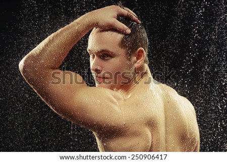 Attractive homosexual. Closeup rear view portrait of young muscled gay man looking over his shoulder through the water drops while taking a shower against black background  - stock photo