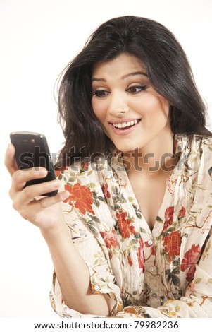 Attractive Indian girl reading or sending an sms - stock photo