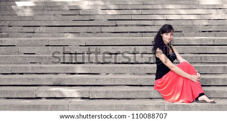 Attractive lady in red dress sitting on steps - stock photo