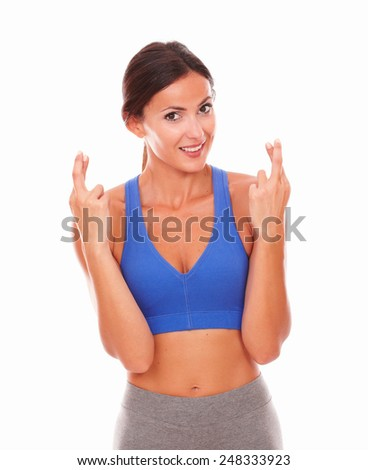 Attractive lady on sport clothing crossing fingers on isolated background - stock photo