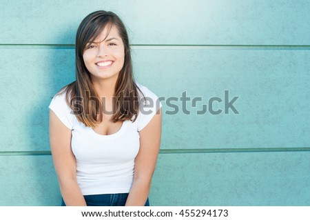 Attractive lady posing and smiling with casual look outside on green wall with copy text area - stock photo