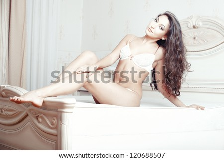 Attractive lady sitting and pamepring in bedroom - stock photo