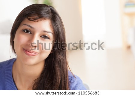 Attractive Latina woman sitting at table in living room with confident expression wearing blue sweater. - stock photo