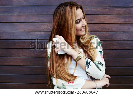 Attractive laughing female standing with mobile phone against wooden wall background with copy space area, pretty casually-dressed hipster woman looking away smiling and feeling so happy in joy - stock photo