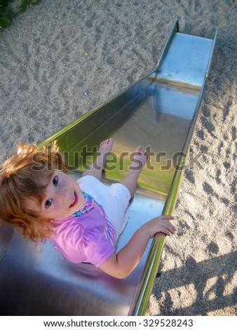 Attractive little girl on playground - stock photo