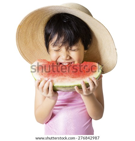 Attractive little girl wearing a big hat while eating watermelon in the studio, isolated on white - stock photo