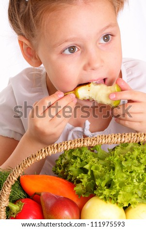 Attractive little girl with vegetables and fruits eating pear - stock photo